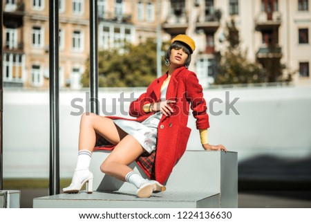 Unnaturally sitting. Artistic young girl in yellow bonnet chilling under the sun in her warm stylish overcoat