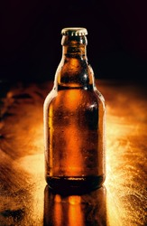 Unopened brown glass bottle of chilled beer backlit on a wooden bar counter , unlabeled for your advertising