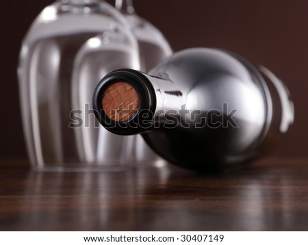 Unopened wine bottle and glasses on wooden surface