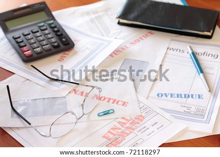 Unpaid Bills on Table with Calculator