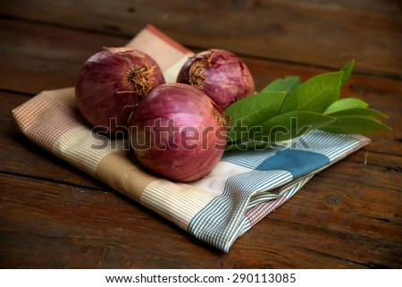 Unpeeled onions on kitchen cloth with fresh laurel leaves on rustic wooden background.
