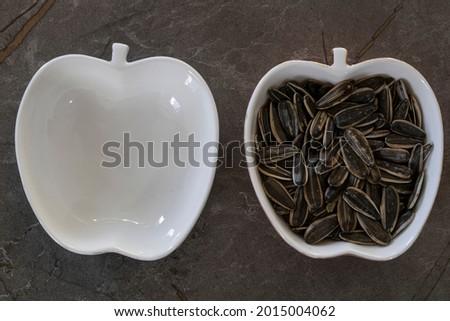 Unpeeled sunflower seeds in bowl isolated on white background. top view, sunflower seeds. core. nuclei. background. black. ay çekirdeği . çekirdek Stok fotoğraf ©