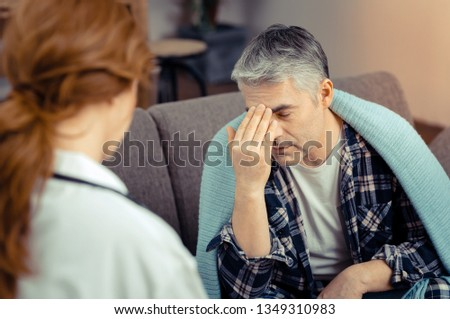 Unpleasant pain. Depressed ill man touching the forehead while describing his type of pain to the doctor
