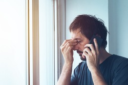 Unpleasant phone call, worried anxious man talking with someone on mobile phone