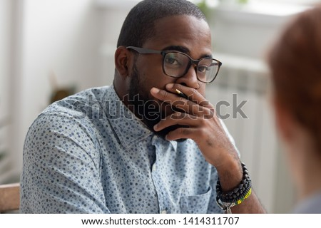 Unpleasantly surprised african-american businessman listening female caucasian coworker with bad news. Human resources generalist keeping hand on mouth has ugly first impression interviewing candidate
