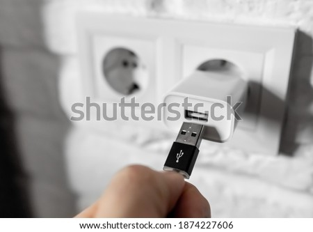Unplugging USB cable from power adapter. Disconnect USB cord from the cellphone charger. Man hold USB plug against wall charger. Plug-in connector into european wall outlet or socket with AC adapter Stock photo ©