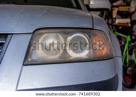 Unpolished dirty front headlight with traces of crushed insects #741689302