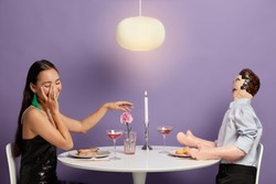 Unreal relationship concept. Happy touched woman stretches hand to inflated male doll, pretends having date, spends free time in restaurant, smiles joyfully. Carefree lonely female simulates relations