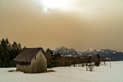 Unreal winter scene in Vorarlberg. Sahara sand is in the air. Trees and a house in the foreground and mountains in the background. yellow colored clouds in the sky dim the light. white snow with trail