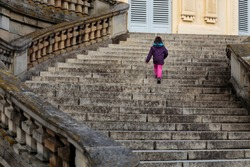 Unrecognisable little girl, modern-day lonely princess walking up majestic curved stairs of empty castle in Europe. Child alone visits historic European site walks up large, decorated flight of stairs