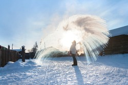 Unrecognisable person pouring hot water up in the sky, sunny winter day in Oymyakon, Yakutia. Boiling water challenge, which instantly freezes, turns into snow if the temperature is extremely cold