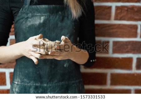 Unrecognisable woman making ceramic bowl in hand. Creative hobby concept. Earn extra money, side hustle, turning hobbies into cash, passion into a job, copy space #1573331533