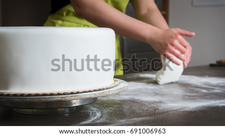 Unrecognisable woman preparing white fondant for cake decorating, hands detail, focus on the cake. DIY,  sequence, step by step, part of series.