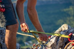unrecognisable young adult man holding on to ropes. young male securing ropes to the rocks for climbing close up
