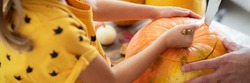 Unrecognisable young girl sitting on kitchen table, helping her father to carve large pumpkin. Halloween family lifestyle background.