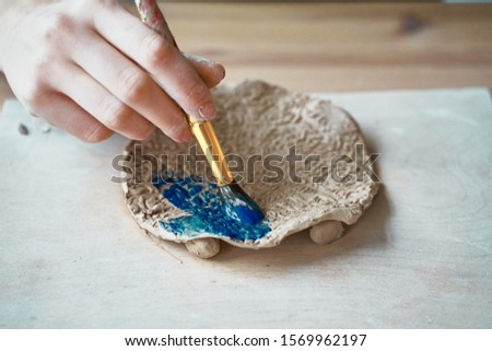 Unrecognised Woman making pattern on ceramic plate, hands close-up, focus on palms with paint brush. Creative hobby concept. Earn extra money, side hustle, turning hobbies into cash, passion into job #1569962197
