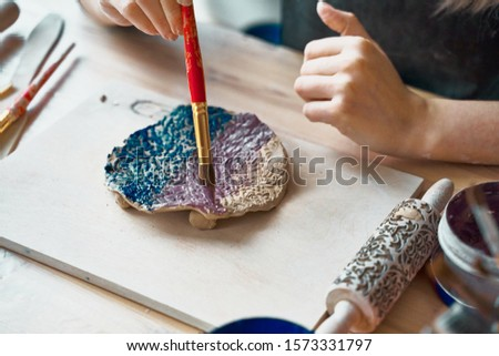 Unrecognised Woman making pattern on ceramic plate, hands close-up, focus on palms with paint brush. Creative hobby concept. Earn extra money, side hustle, turning hobbies into cash, passion into job #1573331797