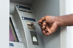 Unrecognizable african man putting credit card into ATM outdoor