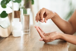 Unrecognizable African Woman Taking Beauty Supplements For Glowing Skin, Holding Omega-3 Fish Oil Capsules In Hands, Side View