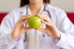 Unrecognizable Asian expert nutritionist showing an organic green apple close up, nutrition consultant portrait. Healthcare and healthy eating for healthy people concept.