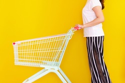 Unrecognizable Asian girl catching on a shopping cart or trolley, shoot on bright yellow background in studio. Woman holding and pushing on a vintage shopping cart close up. Woman shopping concept.