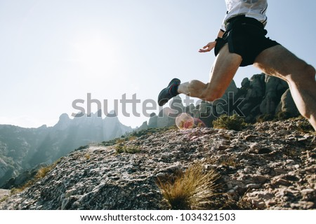 Unrecognizable athlete or sports enthusiast with strong legs with muscles runs through hard terrain mountain path on ultra trail marathon training or race, beautiful natural park scenery