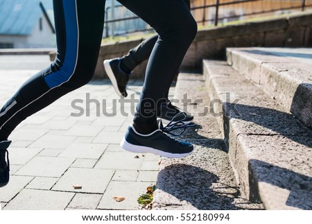 Unrecognizable athletes running on stairs on sunny autumn day. #552180994