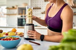Unrecognizable athletic woman using blender while making fruit smoothie in the kitchen.