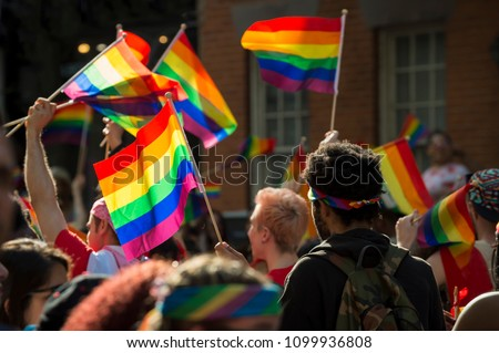 Unrecognizable backlit crowd with rainbows flags and signs in the annual Pride Parade as it passes through Greenwich Village. #1099936808