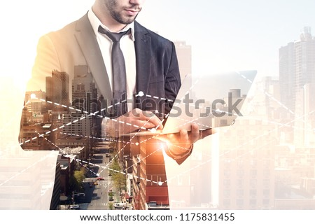 Unrecognizable bearded businessman in suit and tie holding his laptop standing against graphs over morning cityscape. Stock market and fintech concept. Toned image double exposure copy space
