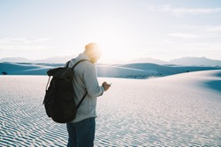 Unrecognizable bearded male traveler in casual clothes and hat and backpack standing on sand and browsing smartphone in White Sands National Park