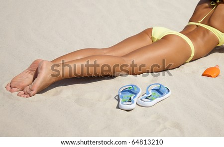 Unrecognizable beautiful young woman in bikini lying and sunning on the beach under the bright sun