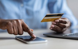 Unrecognizable Black Lady Browsing Mobile Banking App On Smartphone And Holding Credit Card, Paying Bills In Internet, Shopping Online, Transferring Money, Cropped Image, Closeup Shot