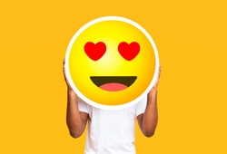 Unrecognizable black man hiding face against in love emoticon emoji, holding big illustrated smile sticker over yellow background, copy space