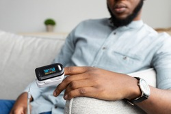 Unrecognizable Black Man With Pulse Oximeter On Hand Measuring Oxygen Saturation Level At Home. Pulseoxymeter Medical Device, Pulseoxymetry Clip Machine Monitorin Ox Rate. Cropped, Selective Focus