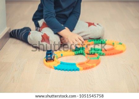 Unrecognizable boy making a trail and playing with car toy on the floor. #1051545758