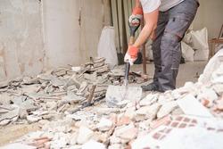 Unrecognizable builder collecting construction debris with a shovel. House renovation.