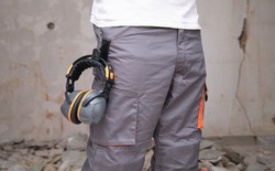 Unrecognizable builder with hearing protection hanging from the trousers. Safety at work concept.