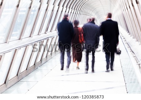 unrecognizable business people walking on a pedestrian bridge with a glass dome