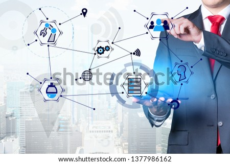 Unrecognizable businessman holding tablet computer and working with GUI interface over cityscape background. Concept of hi tech in business. Double exposure #1377986162