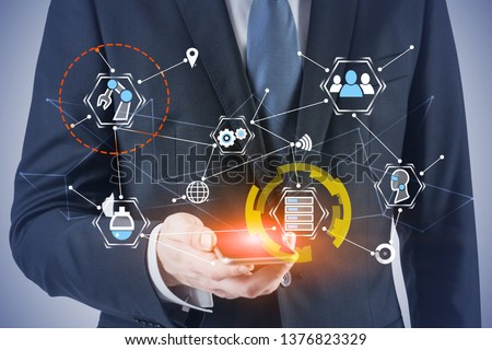 Unrecognizable businessman in suit looking at smartphone with double exposure of GUI and network hologram. Concept of hi tech in business. Toned image #1376823329