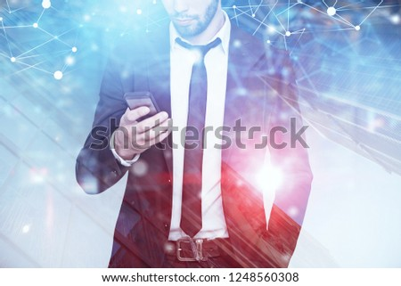 Unrecognizable businessman looking at his smartphone screen standing over skyscraper background with double exposure of network hologram. Toned image