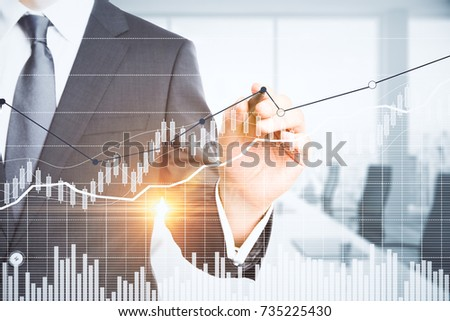 Unrecognizable businessman pointing at abstract business chart on blurry office interior background. Close up. Economy concept. Double exposure  #735225430