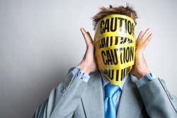 Unrecognizable businessman pressing his hands to his head, wrapped in yellow and black caution tape
