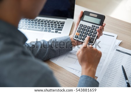 Unrecognizable businessman using calculator