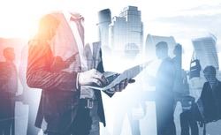 Unrecognizable businessman with laptop and his colleague silhouettes over cityscape background. Concept of teamwork and business lifestyle. Toned image double exposure