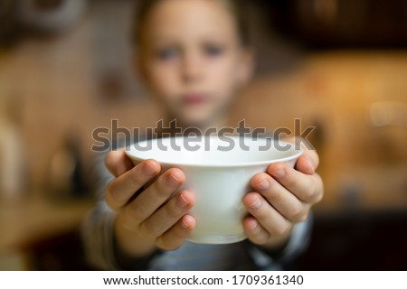 Unrecognizable child girl reaching out hands holding white empty bowl plate offering food or asking for food. Shallow focus. Giving concept. Hungry children Foto stock ©