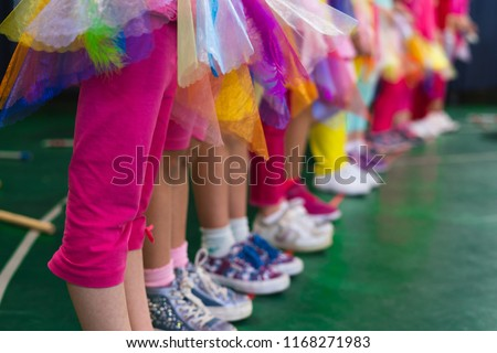 Unrecognizable children perform at school play. Arranged in a row with shoes and colorful stage dresses.