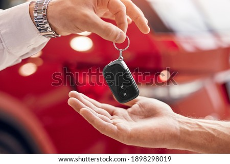Unrecognizable client receiving keys of rent vehicle from manager against red vehicle in dealership