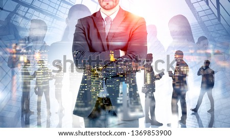 Unrecognizable confident young business leader standing over skyscraper background with his coworkers using gadgets and talking. Concept of leadership. Toned image double exposure